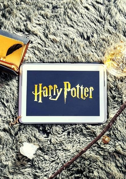 Harry Potter logo on tablet surrounded by trinkets