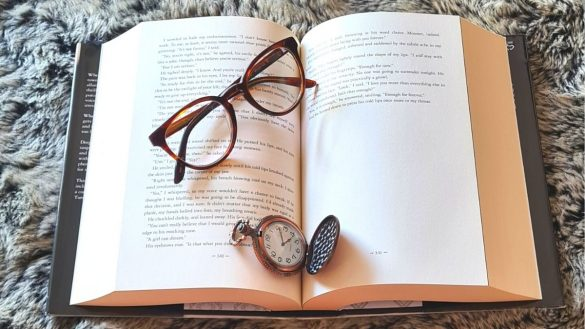 Book with reading glasses and a pocket watch on a soft fur rug