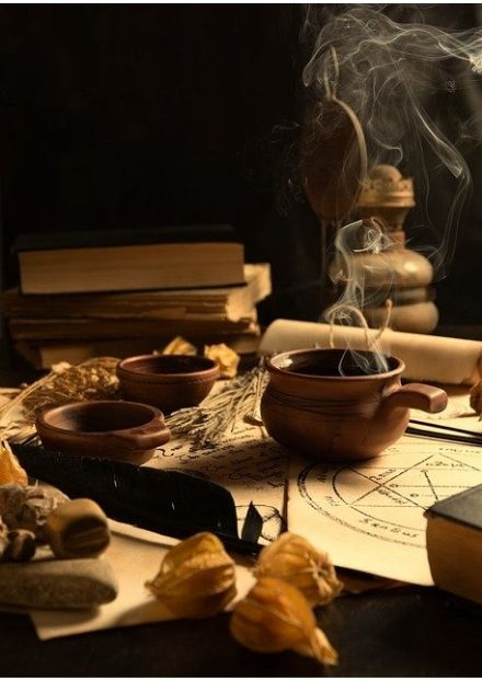 Hot drink on table with magical trinkets and stack of books in background